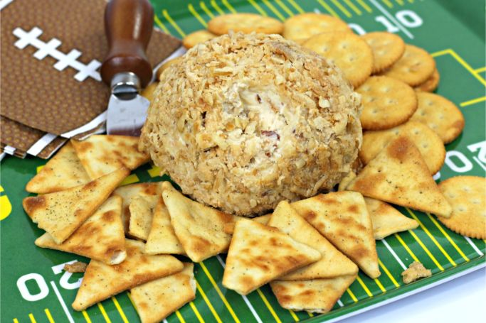 French onion cheese ball with two kinds of crackers on a football-themed background
