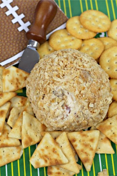 french onion cheese ball with pita chips on a football-themed background