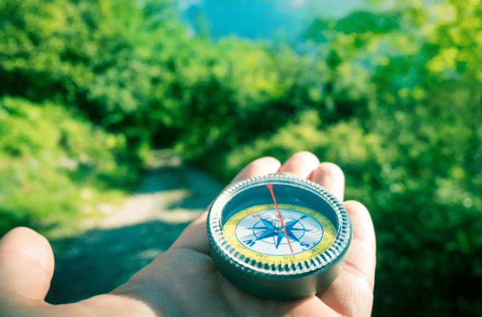 compass in hand on a hiking trail