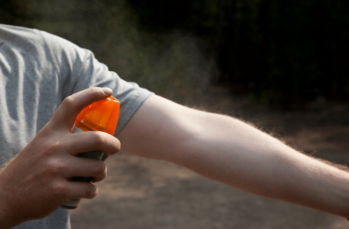 spraying an arm with bug spray