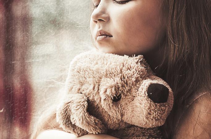 sad child hugging stuffed dog