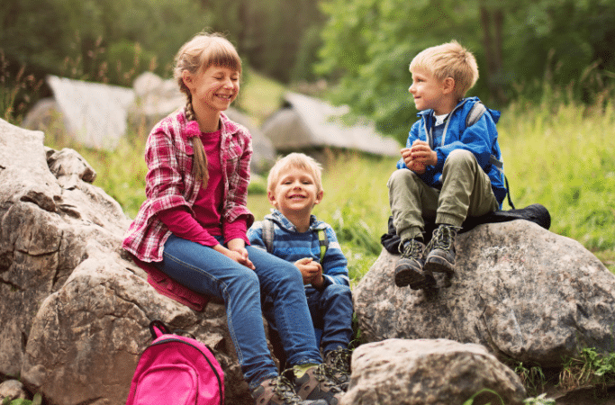 kids resting on rocks during a hike