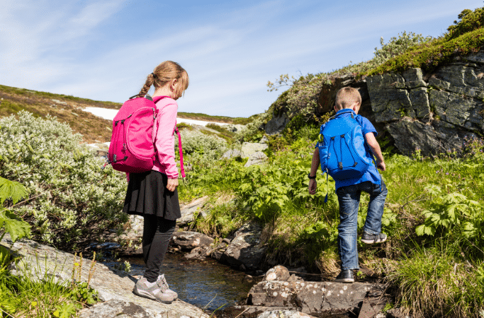 kids carrying backpacks while hiking
