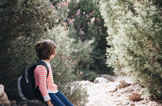 child sitting on a rock on a hiking trail